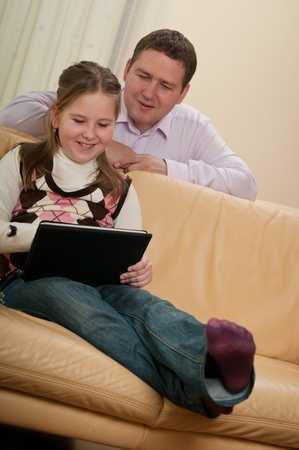 Child playing with tablet - father  watching photo