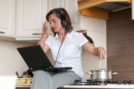 Multitasking - preparing meal and working Stock Photo - 13649582