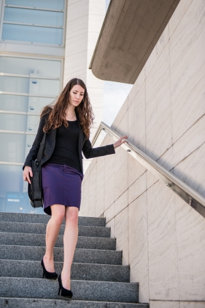 skirt suit: Business woman walking in hurry on stairs