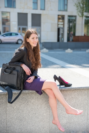 skirt suit: Business woman relaxing in street Stock Photo