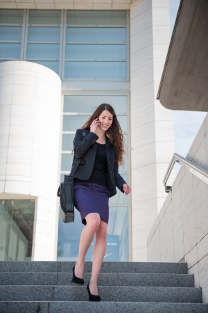 Business woman walking on stairs calling phone Stock Photo - 13649549