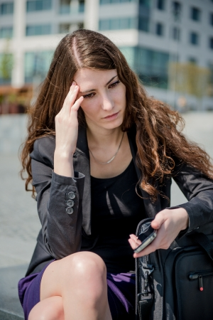 young woman sitting: Problems - business woman reading message on phone