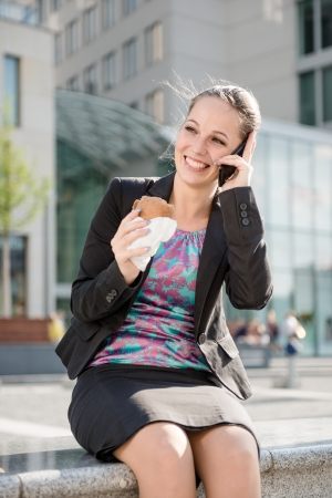 Business woman calling phone and eating photo