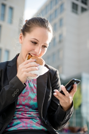 Business woman eating and working with phone photo