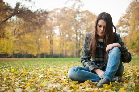 mujer pensativa: Mujer joven en la depresión al aire libre Foto de archivo