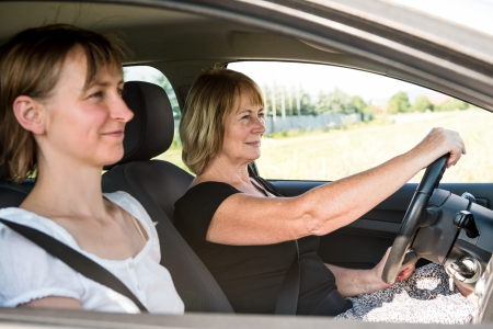 Senior woman with daughter driving car photo