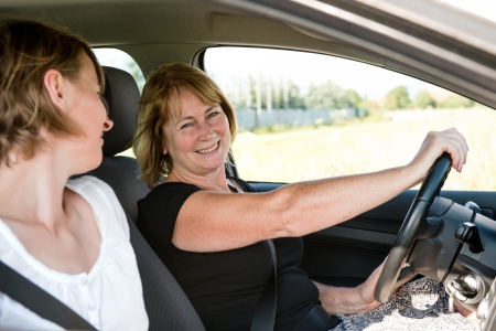 Mature woman with daughter driving car photo
