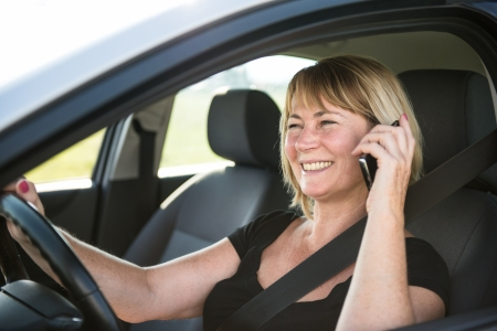 Mature woman driving car and calling photo