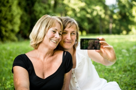 mature old generation: Senior mother with child taking picture