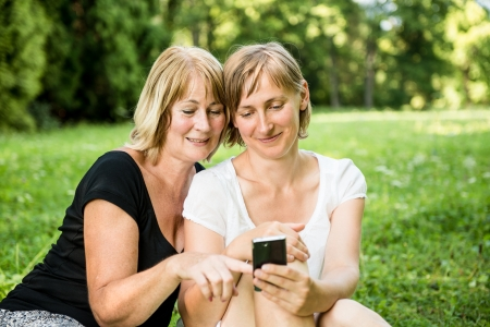 Senior mother and daughter with smartphone photo