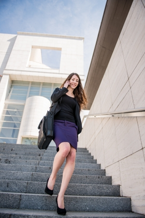 Business woman walking on stairs calling phone photo