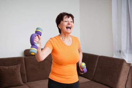 Senior woman exercising with barbells photo