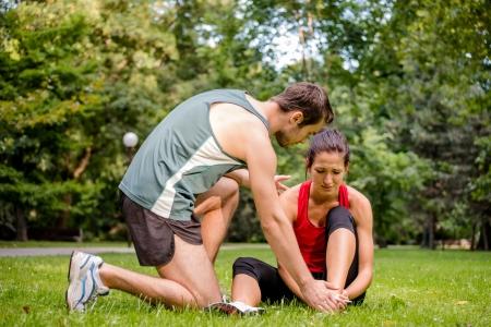 expresion corporal: Lesión Sport - fitness mujer joven sosteniendo su tobillo con dolor, el hombre está ayudando