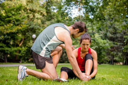 cramped: Sport injury - young fitness woman holding her ankle  with pain, man is helping Stock Photo