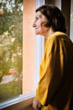 see through: Solitude - senior woman looking through window