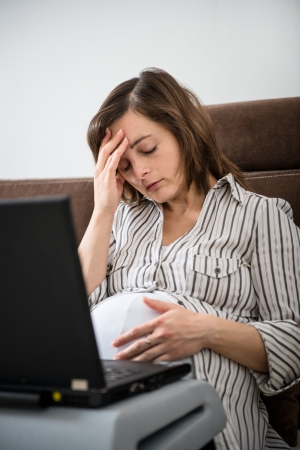 Working pregnant woman with headache photo