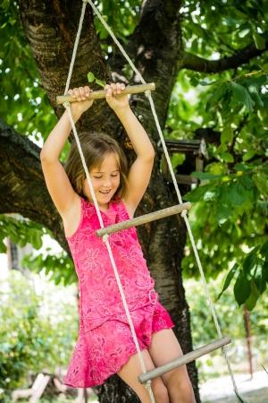 niño trepando: Gilr colgar en la cuerda escalera Foto de archivo