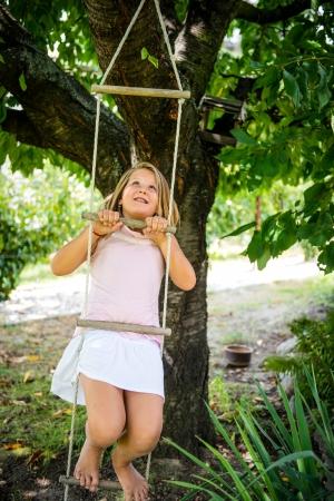 niño escalando: Niña que cuelga en las escaleras de cuerda