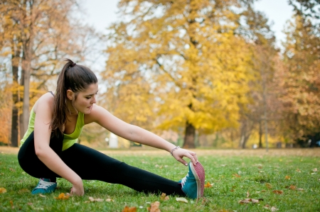 Woman performs stretching before jogging photo