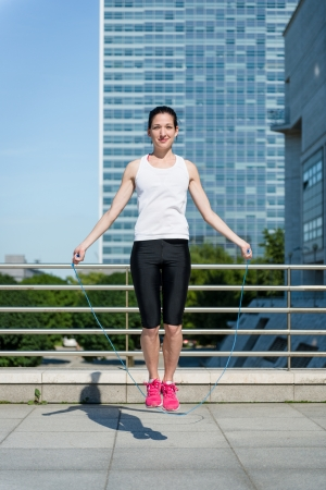 Young sport woman exercising with skipping rope in urban environment photo