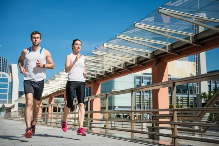 Young sport couple running together in city environment photo