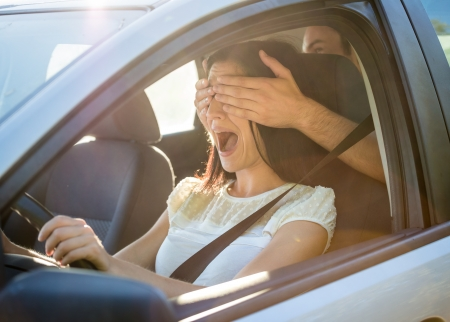 hand covering eye: Young couple in car - man covering eyes of his girlfriend