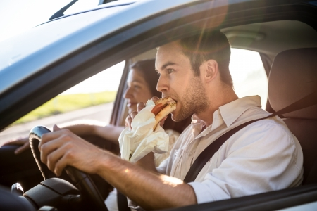eating in: Couple in car - man is driving and eating baguette