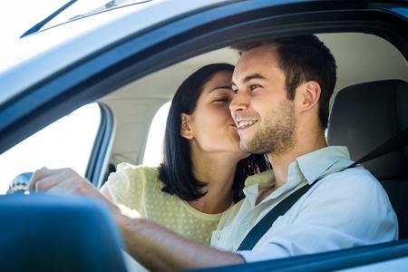 pareja besandose: Pares en coche - mujer joven que besa al hombre en el coche mientras se conduce Foto de archivo