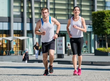 Young sport couple jogging together in city environment photo