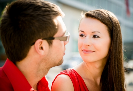 Young couple in love looking to each others eyes - outdoor in street photo