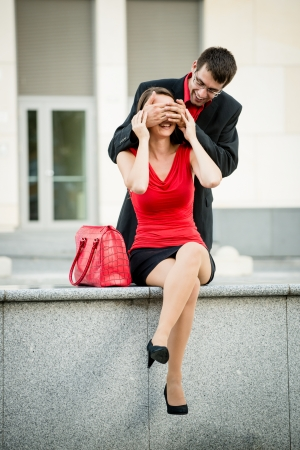 hand covering eye: Young business man surprises waiting woman by covering her eyes