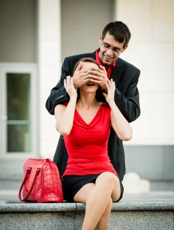 hands behind head: Young business man covering eyes of waiting woman and hiding behind her