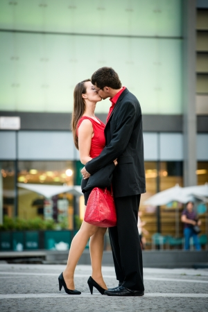 Young business couple dressed in red kiss and welcome each other on street