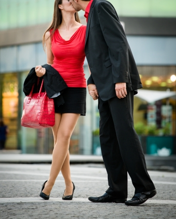 man legs: Young business couple dressed in red kiss and greet each other on street