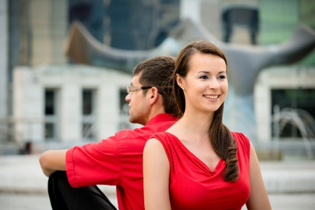 leant: Young business couple relaxing leant with backs on street