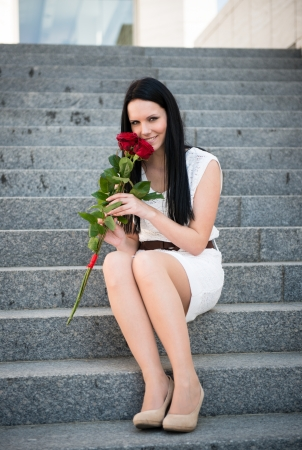 Young beautiful woman with red roses - outdoorf on stairs photo