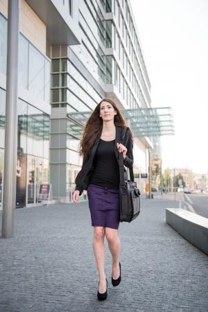 personas en la calle: Joven mujer de negocios en apuro - calle caminando con bolsa de port�til