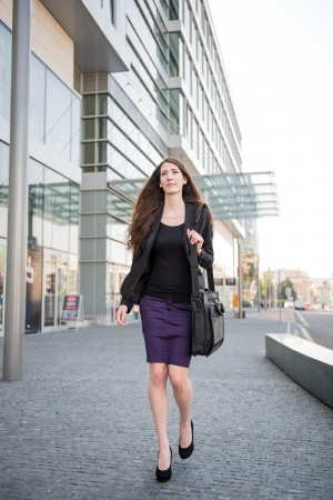 skirt suit: Young business woman in hurry - walking street with notebook bag