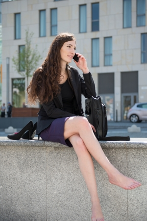 Young smiling business woman sitting in city environment and calling with cellphone photo