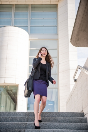 Young smiling business woman walking on stairs calling with mobile phone photo