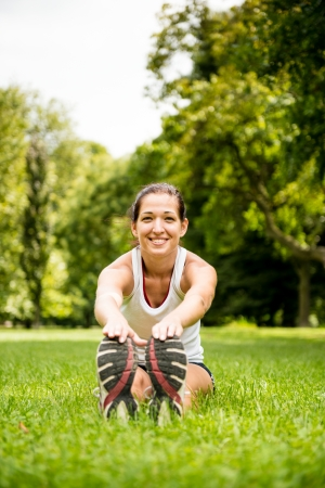 muscle tension: Young fitness woman stretching muscles before sport activity - outdoor in park Stock Photo