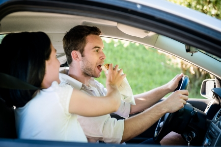 Couple in car - man is driving and woman is feeding him photo