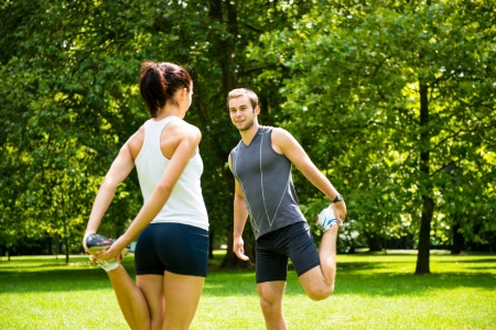 jogging in park: Young couple exercising and stretching muscles before sport activity - outdoor in nature Stock Photo