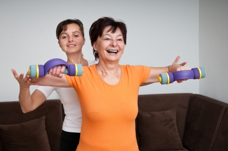 Smiling senior fitness woman exercising with barbells assisted by coach photo