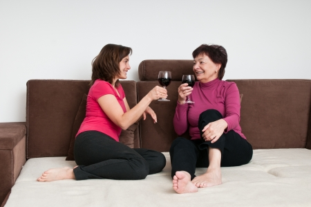 Smiling senior mother with daughter talking and drinking wine on sofa at home photo