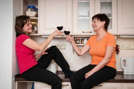 Happy senior mother with daughter talking and drinking wine at kitchen photo
