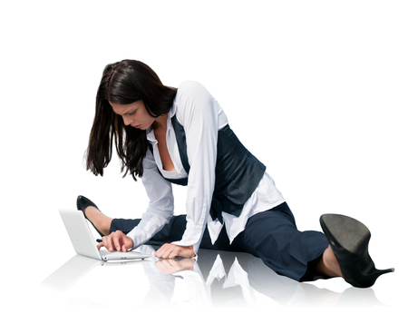 Young business woman in gymnastics pose working with computer - isolated on white photo