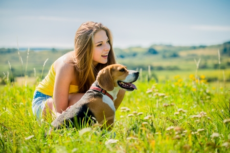 Lifestyle photo of happy young girl with her pet (beagle dog) - outdoor in nature photo