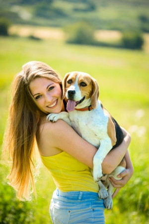 Portrait of young woman with her pet (beagle dog) - outside in nature photo
