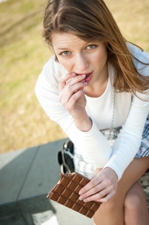 femme triste: D�pression - portrait en plein air de jeune femme inqui�te de manger du chocolat Banque d'images